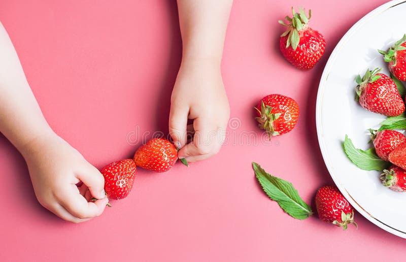 Φράουλα εκμετάλλευσης χεριών παιδιών ` s στο ρόδινο υπόβαθρο, πιάτο των φραουλών κατανάλωση έννοιας υγιής Η τοπ άποψη, επίπεδη βά στοκ φωτογραφία