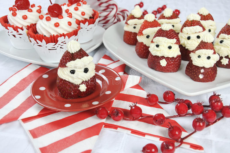 Φράουλα Santas διακοπών Χριστουγέννων με το κόκκινο βελούδο κερασιών cupcakes στοκ φωτογραφία