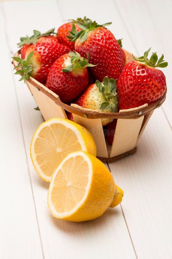 Φράουλες σε ένα μικρά καλάθι και ένα λεμόνι στοκ φωτογραφίες με δικαίωμα ελεύθερης χρήσης