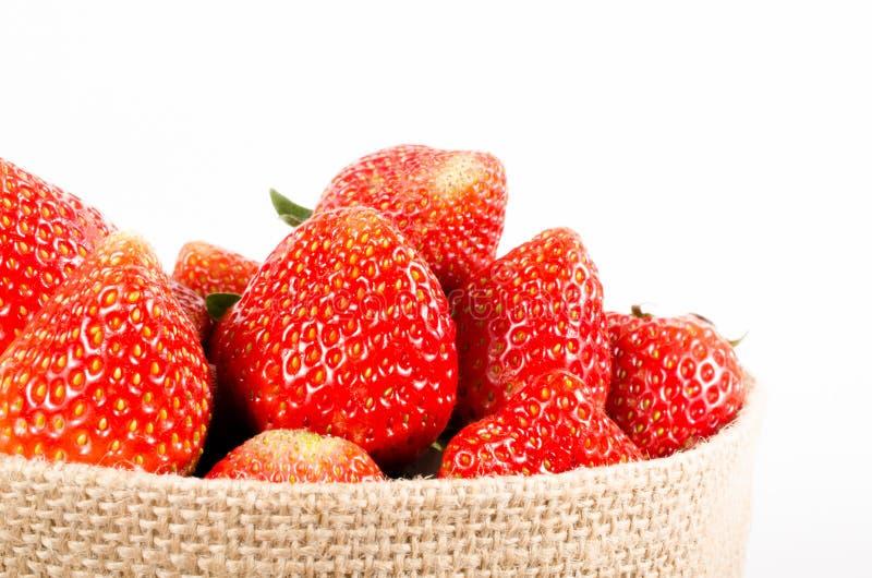 Φράουλες στην τσάντα σάκων στο άσπρο υπόβαθρο στοκ εικόνες με δικαίωμα ελεύθερης χρήσης