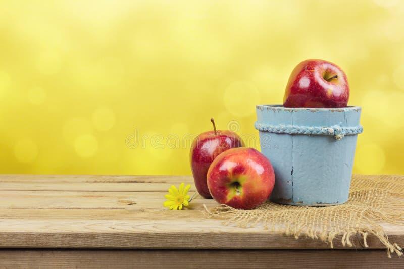 Φρέσκα αγροτικά μήλα στον ξύλινο πίνακα πέρα από το κίτρινο υπόβαθρο bokeh στοκ φωτογραφία με δικαίωμα ελεύθερης χρήσης