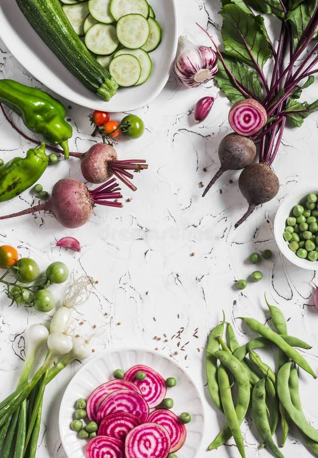 Φρέσκα ακατέργαστα λαχανικά - τεύτλα, πράσινα μπιζέλια και φασόλια, κολοκύθια, πιπέρια, κρεμμύδια, σκόρδο σε ένα ελαφρύ υπόβαθρο  στοκ εικόνες