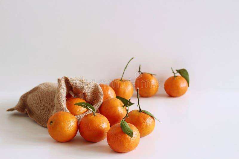 Φρέσκα ακατέργαστα οργανικά Tangerines με τα πράσινα φύλλα στην τσάντα στον άσπρο ξύλινο πίνακα διάστημα αντιγράφων Πλούσιοι των  στοκ φωτογραφία με δικαίωμα ελεύθερης χρήσης