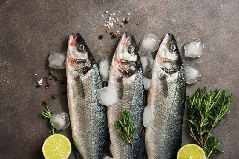 Φρέσκα ακατέργαστα seabass ψάρια με το δεντρολίβανο και ασβέστης σε ένα σκοτεινό καφετί αγροτικό υπόβαθρο r στοκ φωτογραφία