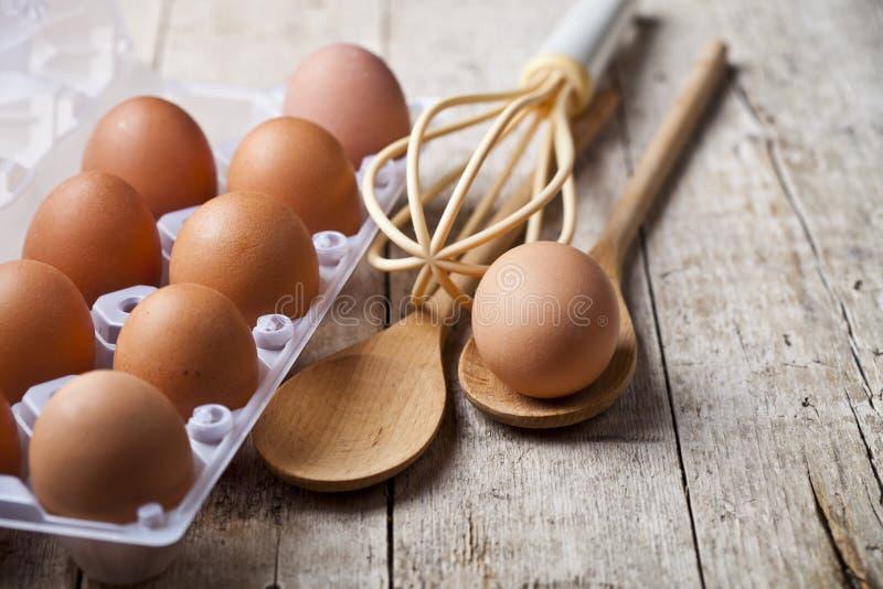 Φρέσκα αυγά κοτόπουλου στο εργαλείο πλαστικών εμπορευματοκιβωτίων και κουζινών στο αγροτικό ξύλινο επιτραπέζιο υπόβαθρο στοκ φωτογραφίες με δικαίωμα ελεύθερης χρήσης