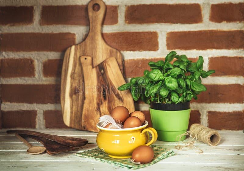 Φρέσκα αυγά, πράσινος βασιλικός και ξύλινα στηρίγματα κουζινών στο τουβλότοιχο β στοκ φωτογραφία με δικαίωμα ελεύθερης χρήσης