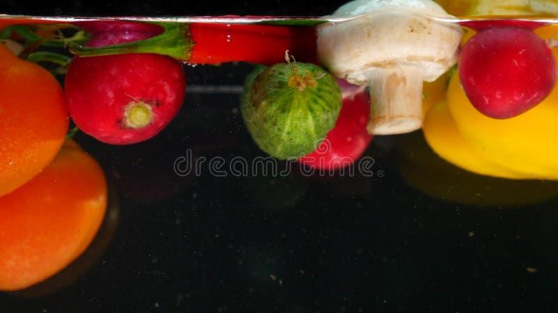 Φρέσκα λαχανικά που πέφτουν με το νερό στο μαύρο υπόβαθρο στοκ φωτογραφίες