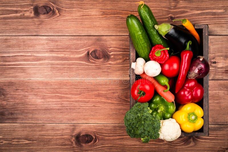 Φρέσκα λαχανικά στο ξύλινο κιβώτιο στο αγροτικό υπόβαθρο στοκ φωτογραφία