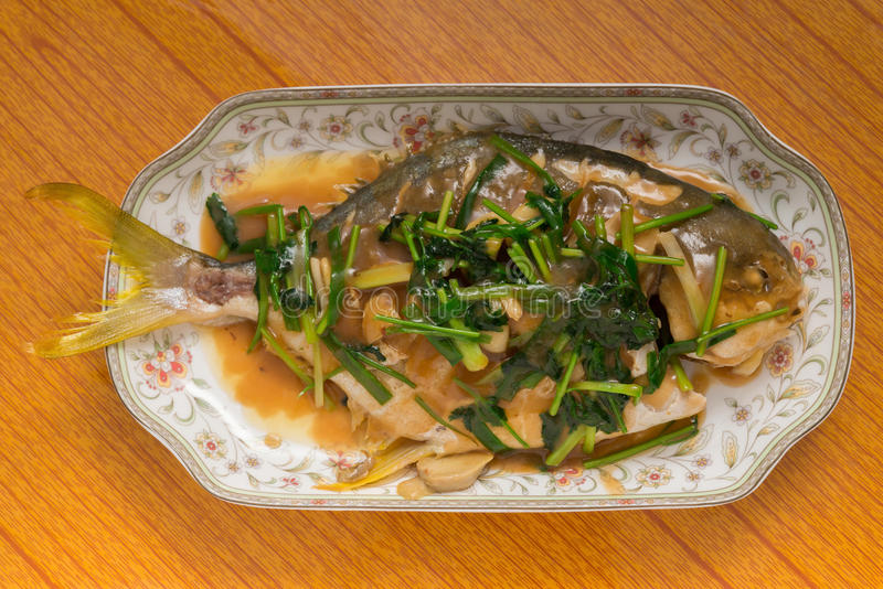 Φρέσκα βρασμένα στον ατμό ολόκληρα ψάρια που καλύπτονται με τα κρεμμύδια & τη σάλτσα χορταριών στοκ φωτογραφία
