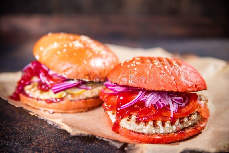 Φρέσκα δύο σπιτικά burgers στον ξύλινο πίνακα πέρα από το σκοτεινό ξύλινο υπόβαθρο στοκ φωτογραφία