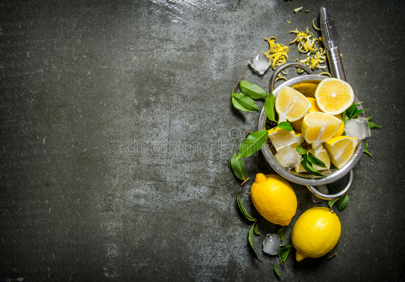 Φρέσκα λεμόνια σε μια κατσαρόλλα με τα φύλλα και την απόλαυση στοκ φωτογραφία