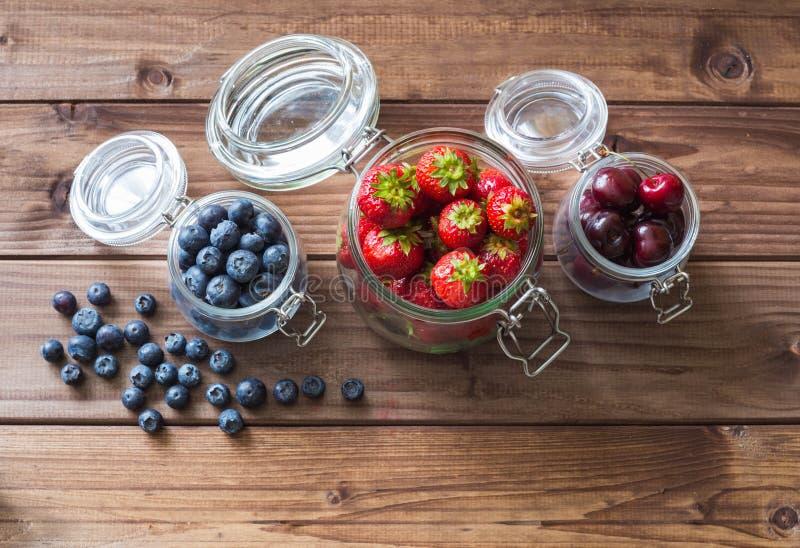 Φρέσκα εποχιακά φρούτα στα βάζα/τα βακκίνια, τις φράουλες και τα κεράσια σε έναν ξύλινο πίνακα στοκ εικόνα