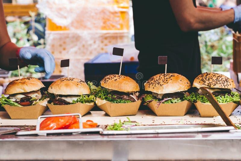Φρέσκα εύγευστα ψημένα στη σχάρα burgers στον πίνακα Burger φεστιβάλ στοκ εικόνες