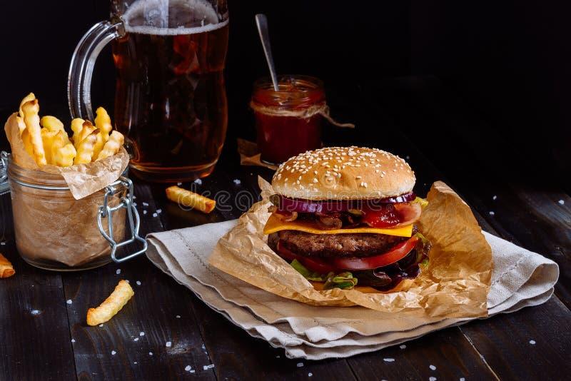 Φρέσκα εύγευστα burgers με τις τηγανιτές πατάτες, τη σάλτσα και την μπύρα στον ξύλινο πίνακα στοκ φωτογραφία με δικαίωμα ελεύθερης χρήσης