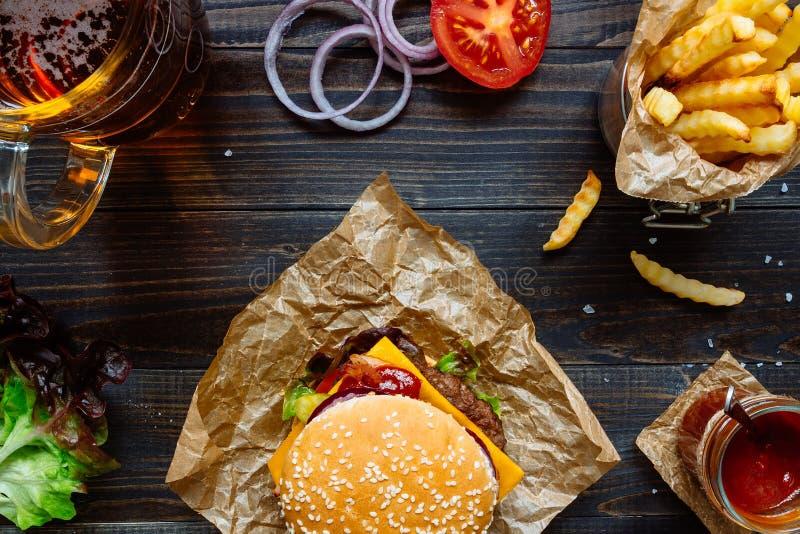 Φρέσκα εύγευστα burgers με τις τηγανιτές πατάτες, τη σάλτσα και την μπύρα στην ξύλινη άποψη επιτραπέζιων κορυφών στοκ φωτογραφία με δικαίωμα ελεύθερης χρήσης
