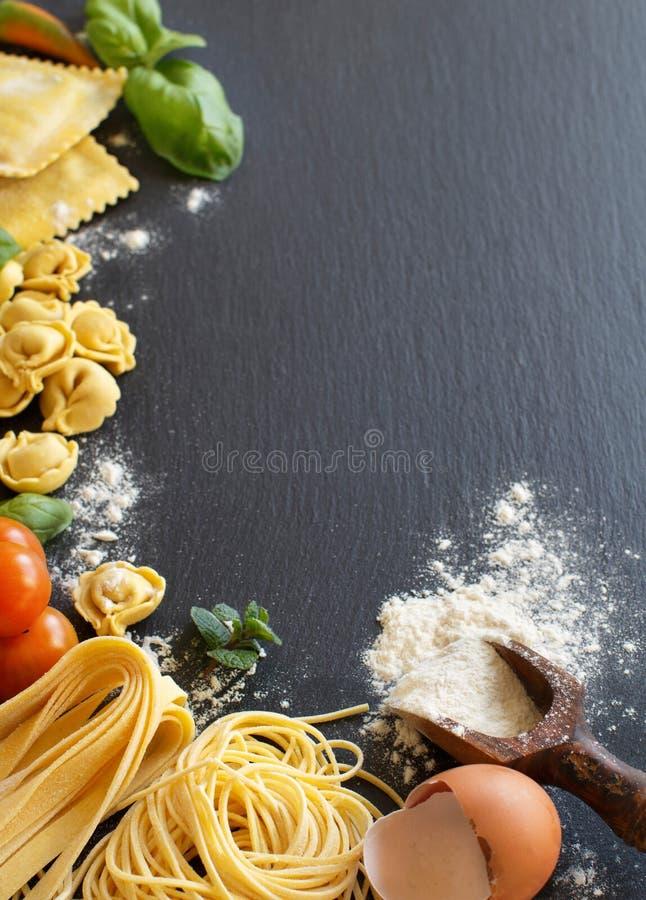 Φρέσκα ζυμαρικά και συστατικά σε έναν σκοτεινό πίνακα στοκ φωτογραφία με δικαίωμα ελεύθερης χρήσης