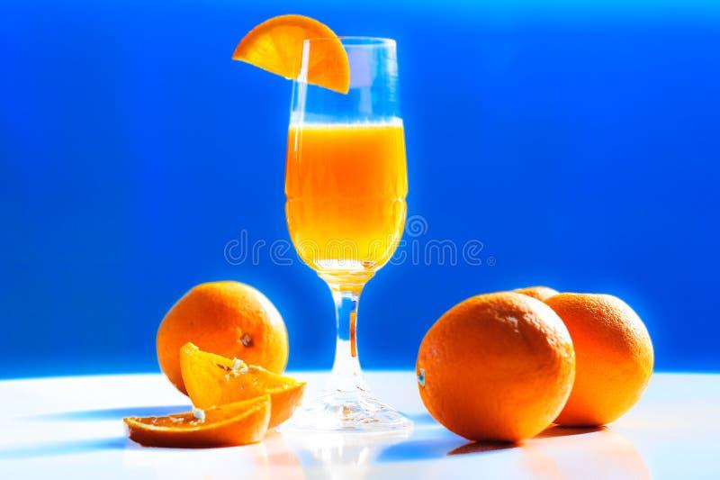 Φρέσκα ζωηρά ζωηρόχρωμα πορτοκάλια και ένα γυαλί κρυστάλλου πολυτέλειας φρέσκου στοκ εικόνα με δικαίωμα ελεύθερης χρήσης
