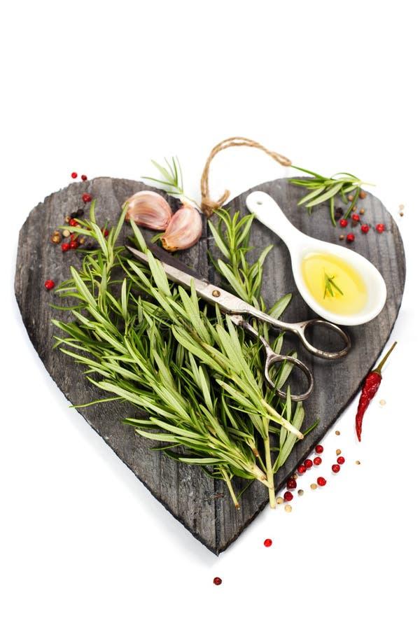 Φρέσκα καρυκεύματα διαμορφωμένο στον καρδιά τέμνοντα πίνακα στοκ φωτογραφίες