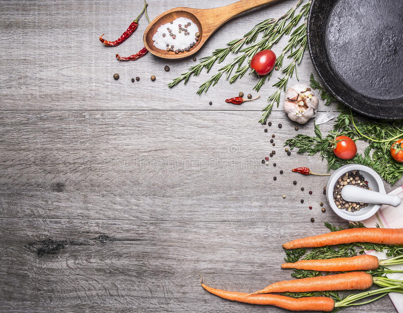 Φρέσκα καρότα από τον κήπο με τα χορτάρια και τα καρυκεύματα με έναν εκλεκτής ποιότητας χυτοσίδηρο που τηγανίζει την παν ξύλινη α στοκ εικόνα