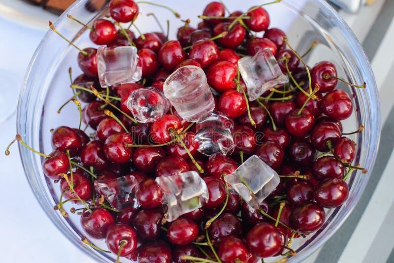 Φρέσκα κόκκινα κεράσια με τον πάγο σε ένα βάζο γυαλιού στοκ εικόνες με δικαίωμα ελεύθερης χρήσης