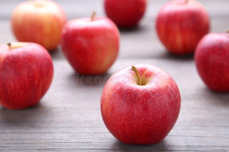 Φρέσκα κόκκινα μήλα σε ένα γκρίζο ξύλινο υπόβαθρο στοκ φωτογραφία