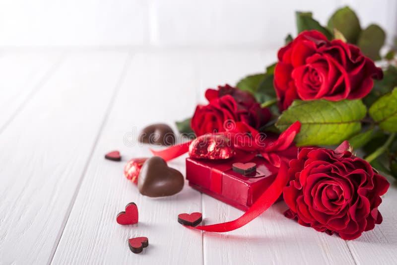 Φρέσκα κόκκινα τριαντάφυλλα και κιβώτιο δώρων στον ξύλινο πίνακα στοκ φωτογραφία με δικαίωμα ελεύθερης χρήσης