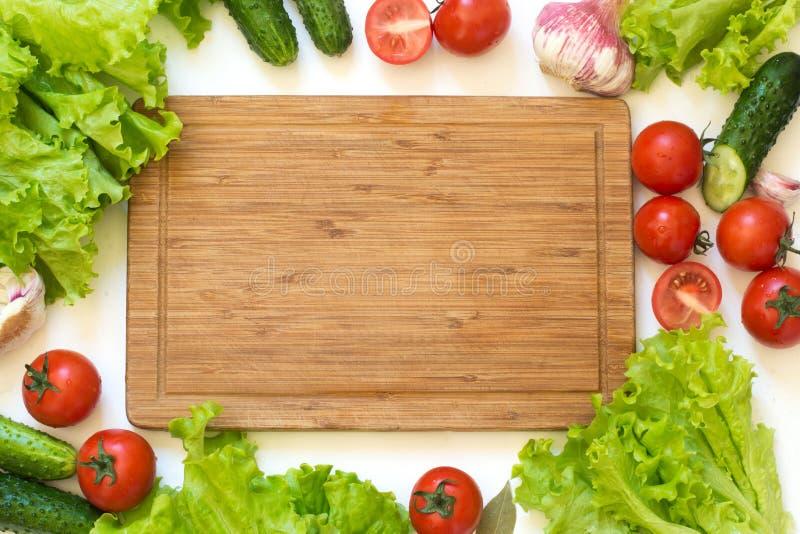 Φρέσκα λαχανικά για τη σαλάτα Ακατέργαστο πράσινο μαρούλι, πράσινα, ντομάτα Τοπ όψη Διάστημα αντιγράφων στον ξύλινο τέμνοντα πίνα στοκ εικόνα
