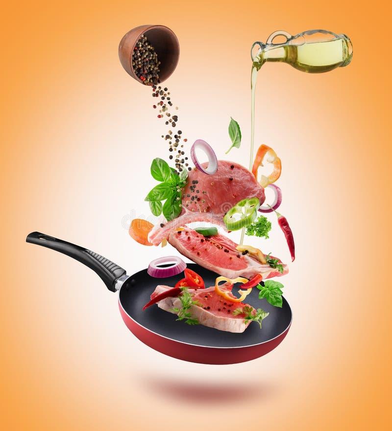 Φρέσκα λαχανικά με τα κομμάτια του κρέατος βόειου κρέατος, τα καρυκεύματα και το πέταγμα πετρελαίου απεικόνιση αποθεμάτων