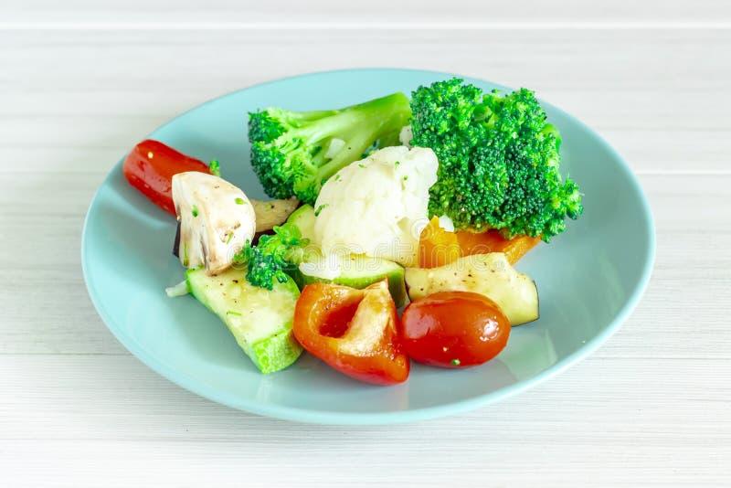 Φρέσκα λαχανικά στο μπλε πιάτο στο άσπρο υπόβαθρο r στοκ εικόνες