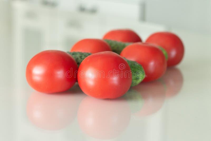 Φρέσκα ντομάτες και αγγούρι σε έναν άσπρο πίνακα κουζινών γυαλιού Φρέσκα συστατικά οργανικής τροφής r στοκ εικόνα