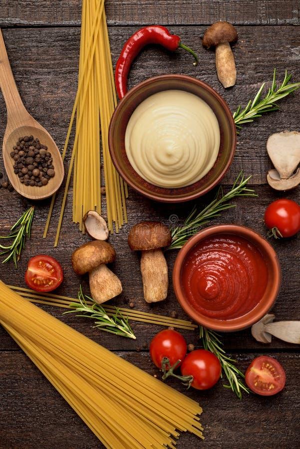 Φρέσκα νόστιμα συστατικά για το υγιές μαγείρεμα με το κόκκινο και τη σάλτσα και τα ζυμαρικά μανιταριών στοκ φωτογραφίες