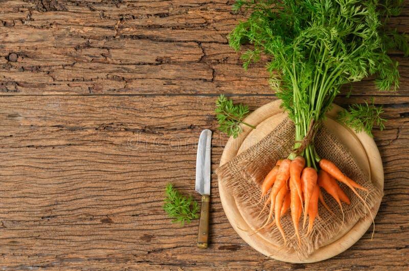 Φρέσκα οργανικά καρότα με τα πράσινα φύλλα στο παλαιό ξύλο στοκ φωτογραφία με δικαίωμα ελεύθερης χρήσης