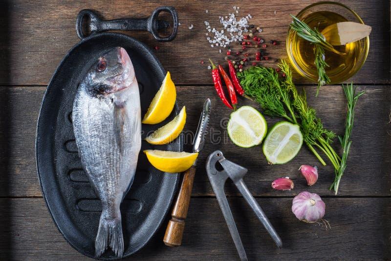 Φρέσκα ολόκληρα ψάρια θάλασσας στο αγροτικό τηγάνι σιδήρου, έννοια μαγειρέματος στοκ φωτογραφία