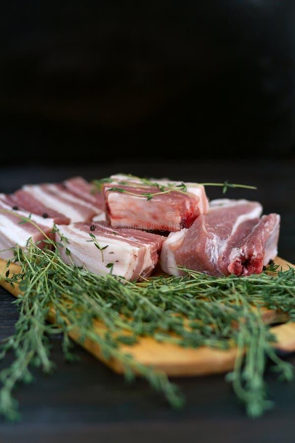 Φρέσκα πλευρά χοιρινού κρέατος, περικοπή στα κομμάτια με τα χορτάρια και τα καρυκεύματα στοκ φωτογραφίες με δικαίωμα ελεύθερης χρήσης