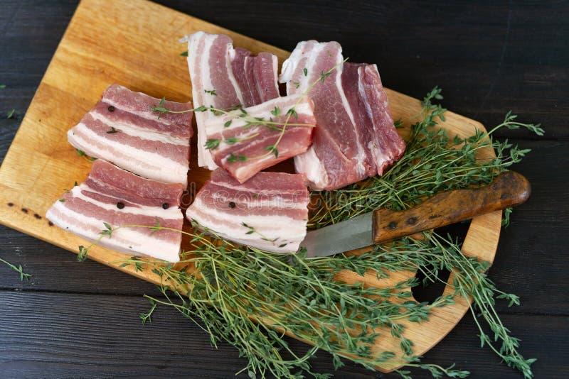Φρέσκα πλευρά χοιρινού κρέατος, περικοπή στα κομμάτια με τα χορτάρια και τα καρυκεύματα στοκ εικόνες