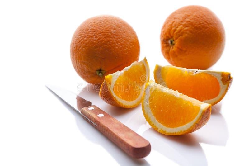 Φρέσκα πορτοκάλια και μαχαίρι Απομονωμένη σύνθεση στο άσπρο υπόβαθρο με τη σκιά στοκ εικόνες