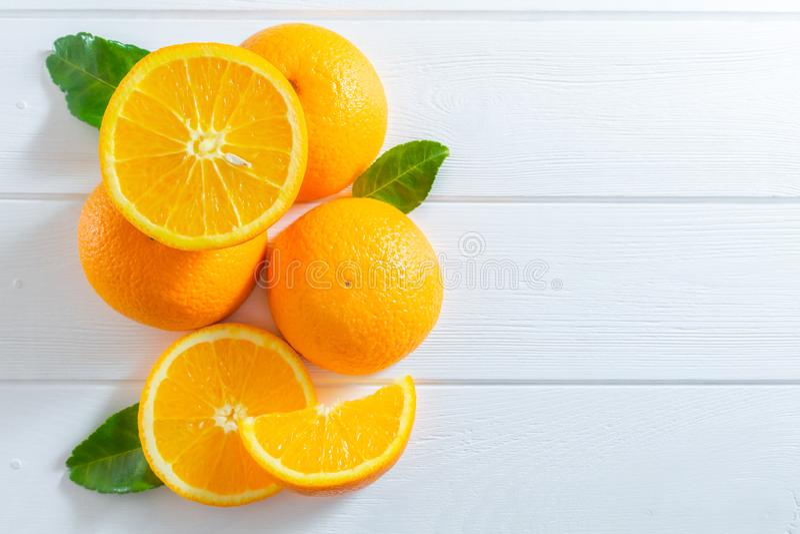 Φρέσκα πορτοκάλια και πράσινα φύλλα στον άσπρο ξύλινο πίνακα Επίπεδος-βάλτε, τοπ άποψη στοκ φωτογραφία