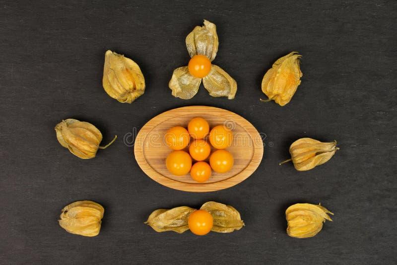 Φρέσκα πορτοκαλιά physalis στην γκρίζα πέτρα στοκ εικόνες