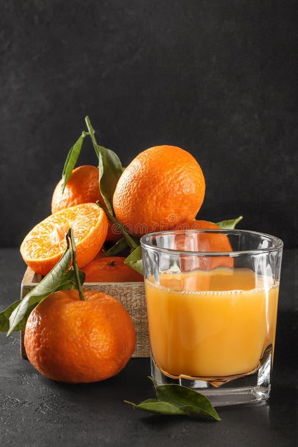 Φρέσκα πορτοκαλιά tangerines με τα πράσινα φύλλα και το γυαλί χυμού στοκ φωτογραφία