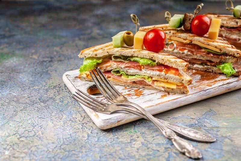 Φρέσκα σάντουιτς βόειου κρέατος με τις ντομάτες και πράσινη σαλάτα και δύο δίκρανα Παραδοσιακό πρόγευμα ή μεσημεριανό γεύμα στοκ φωτογραφία με δικαίωμα ελεύθερης χρήσης