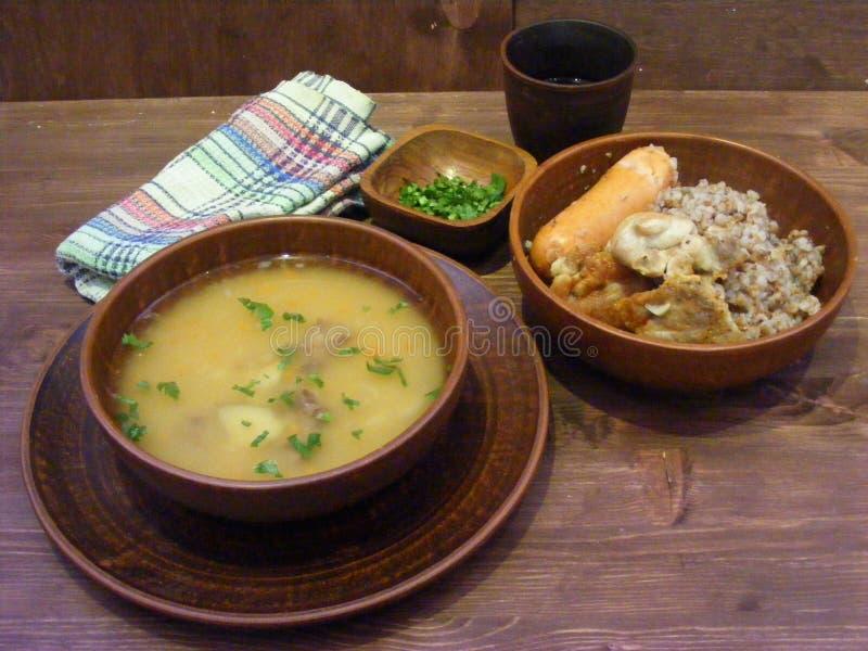 Φρέσκα σούπα και φαγόπυρο στα πιάτα αργίλου στον ξύλινο πίνακα στοκ εικόνα με δικαίωμα ελεύθερης χρήσης