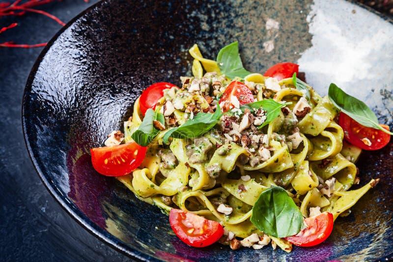 Φρέσκα σπιτικά ιταλικά ζυμαρικά με τις ντομάτες, το βασιλικό και το μοσχαρίσιο κρέας, παρμεζάνα Περίβολος επάνω στην εκλεκτική εσ στοκ φωτογραφία