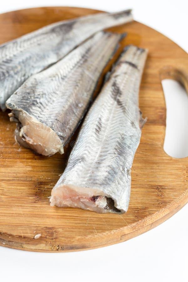 Φρέσκα τεμαχισμένα δίχτυα ψαριών μπακαλιάρων στο cuting ξύλινο πίνακα στοκ φωτογραφίες με δικαίωμα ελεύθερης χρήσης