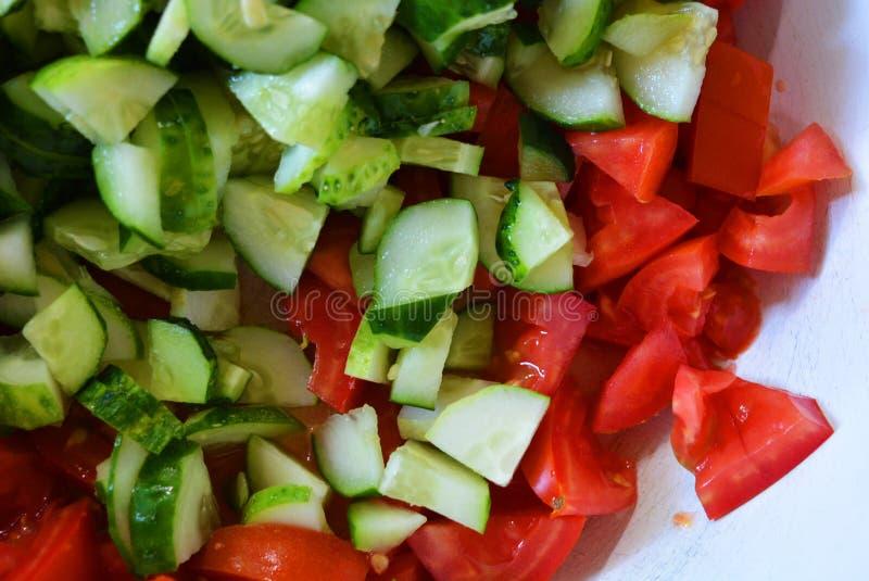 Φρέσκα υγιή λαχανικά, μικρές φέτες των πράσινων αγγουριών και κόκκινες ντομάτες για τη θερινή σαλάτα, συστατικά για τη σαλάτα στοκ φωτογραφίες με δικαίωμα ελεύθερης χρήσης