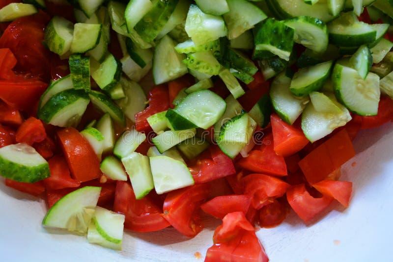 Φρέσκα υγιή λαχανικά, μικρές φέτες των πράσινων αγγουριών και κόκκινες ντομάτες για τη θερινή σαλάτα, συστατικά για τη σαλάτα στοκ εικόνες με δικαίωμα ελεύθερης χρήσης