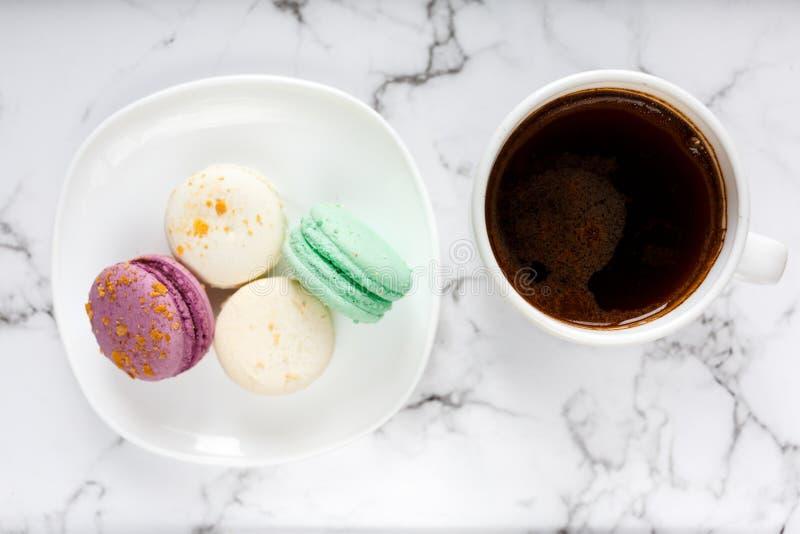 Φρέσκα φλυτζάνι και πιάτο καφέ με τα ζωηρόχρωμα macarons στο μαρμάρινο επιτραπέζιο υπόβαθρο Εύγευστο διάλειμμα στοκ εικόνες