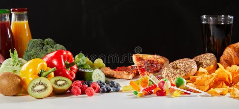 Φρέσκα φρούτα και λαχανικά δίπλα στο γρήγορο φαγητό στοκ εικόνα