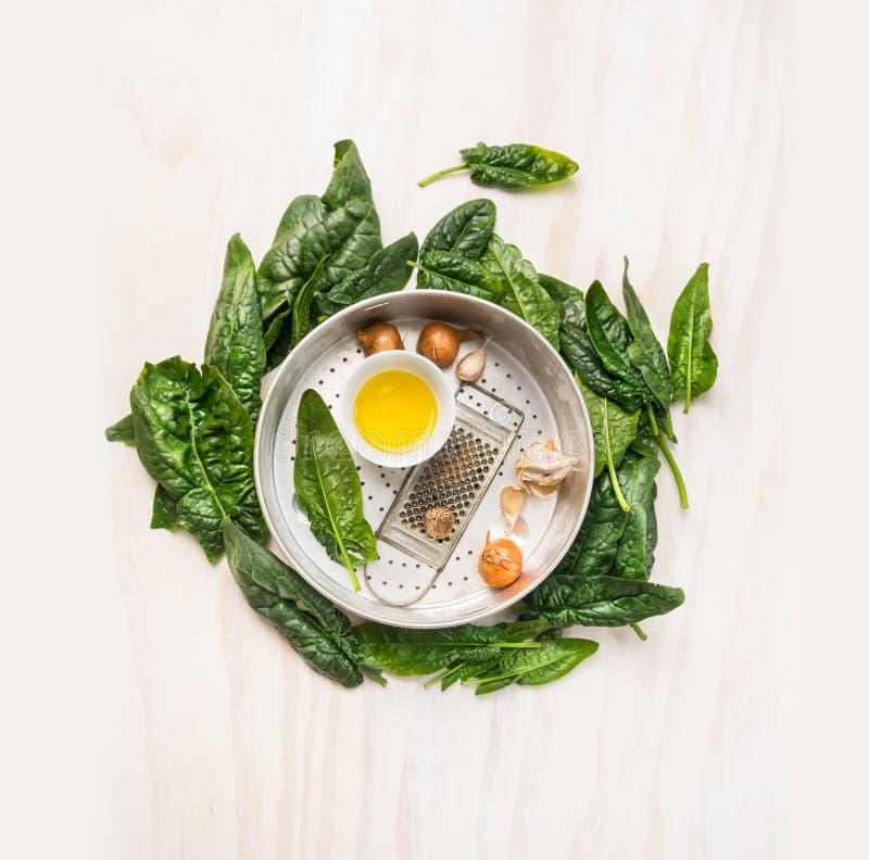 Φρέσκα φύλλα σπανακιού γύρω από το τρυπητό με το μαγείρεμα των συστατικών στο άσπρο ξύλινο υπόβαθρο στοκ φωτογραφία με δικαίωμα ελεύθερης χρήσης
