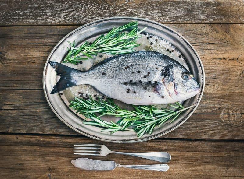 Φρέσκα ψάρια θάλασσας (τσιπούρα) σε ένα πιάτο μετάλλων με το δεντρολίβανο και το spi στοκ φωτογραφίες με δικαίωμα ελεύθερης χρήσης