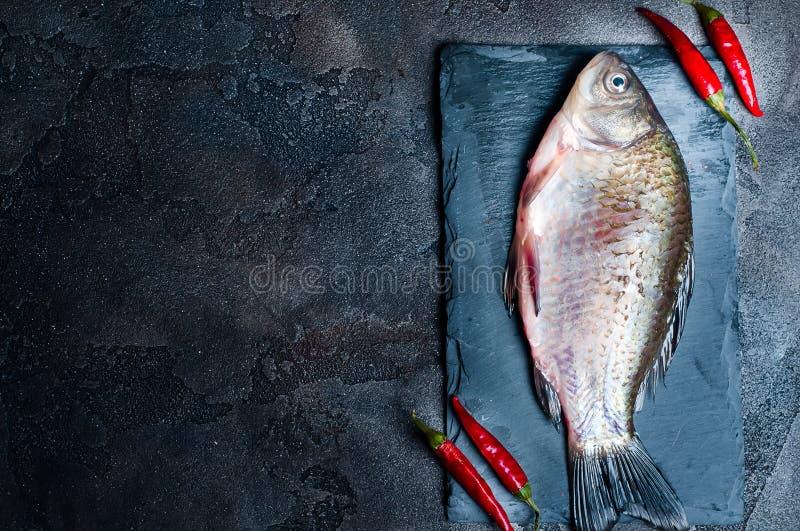 Φρέσκα ψάρια με τα καρυκεύματα σε έναν πίνακα πετρών στοκ εικόνα